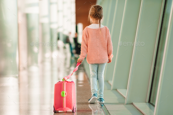 Adorable little girl in airport with her luggage waiting for boarding - Stock Photo - Images