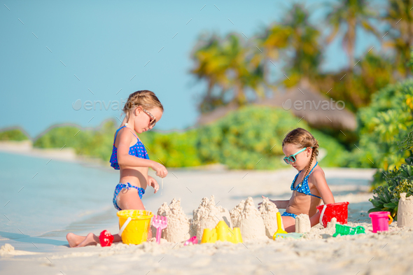 Two kids making sand castle and having fun at tropical beach - Stock Photo - Images