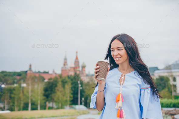 Happy young urban woman drinking coffee in european city - Stock Photo - Images