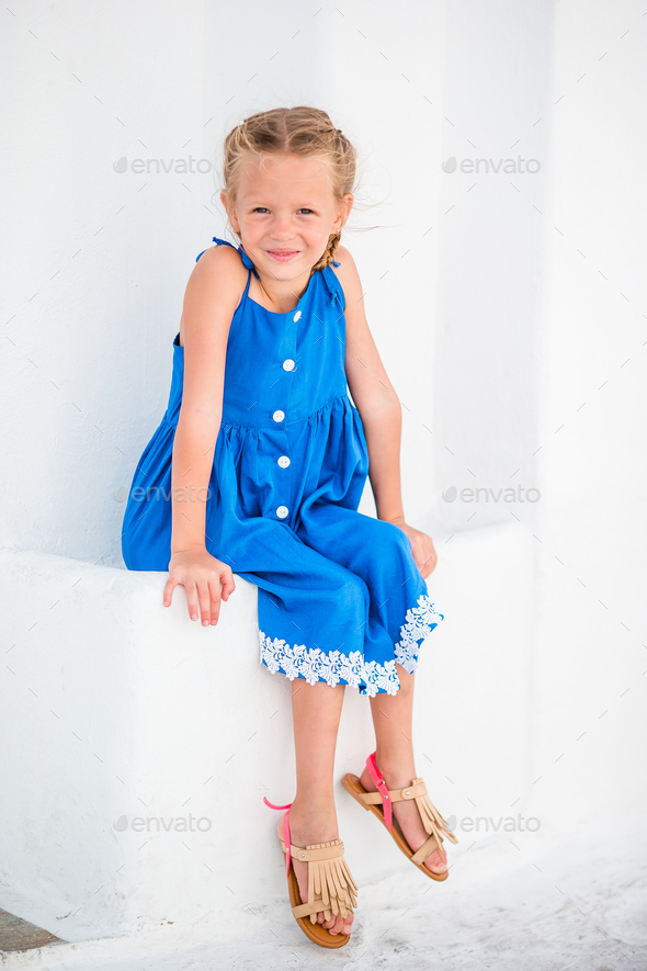 Girl in blue dresses having fun outdoors on Mykonos streets - Stock Photo - Images