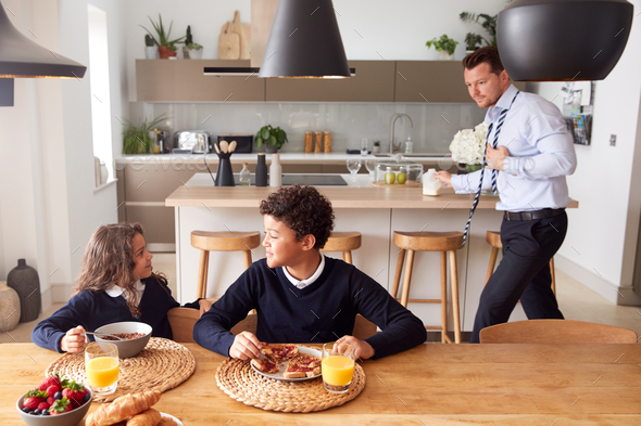 Children Wearing School Uniform Eating Breakfast As Father Gets Ready For Work - Stock Photo - Images