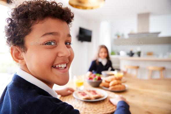 Portrait Of Children Wearing Uniform In Kitchen Eating Breakfast Before Going To School - Stock Photo - Images