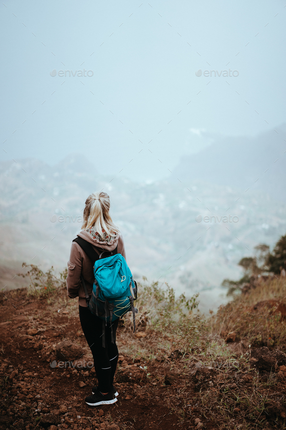 Female hiker looking down over a vertiginous misty ridge on the route to Coculi. Santo Antao Cape - Stock Photo - Images