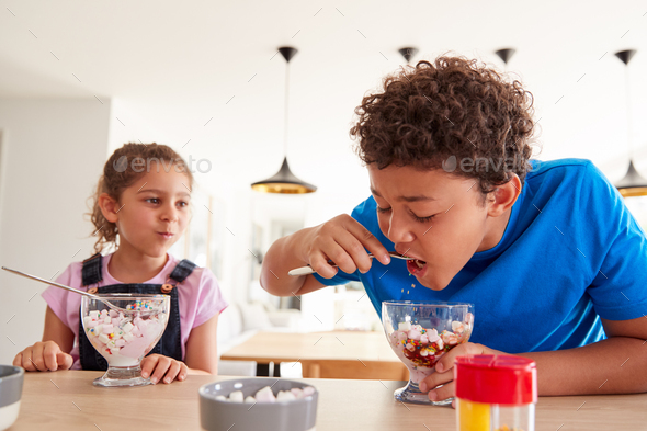 Children In Kitchen At Home Eating Ice Cream Desserts They Have Made - Stock Photo - Images