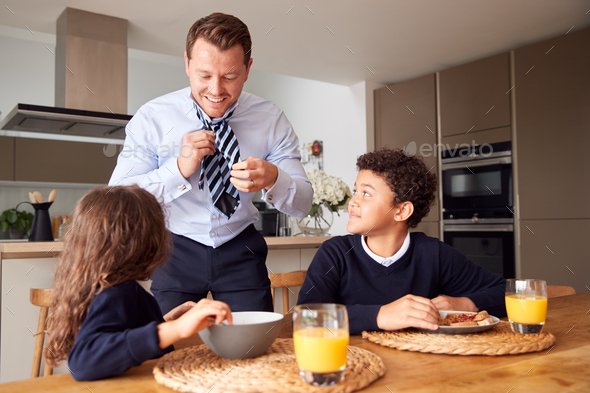 Children Eating Breakfast Before School As Father Get Ready For Work In Office - Stock Photo - Images