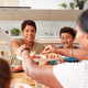 Father Serving As Multi-Generation Mixed Race Family Eat Meal Around Table At Home Together - PhotoDune Item for Sale