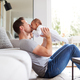 Loving Father Lifting And Kissing 3 Month Old Baby Daughter In The Air In Lounge At Home - PhotoDune Item for Sale