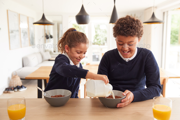 Children At Kitchen Counter Eating Sugary Breakfast Before Going To School - Stock Photo - Images