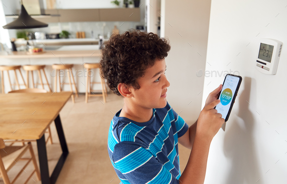 Boy Changes Temperature On Central Heating Thermostat Control Using Mobile Phone App - Stock Photo - Images
