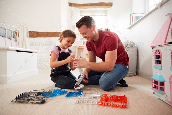 Father And Daughter In Bedroom Building Robot Kit Together - Stock Photo - Images
