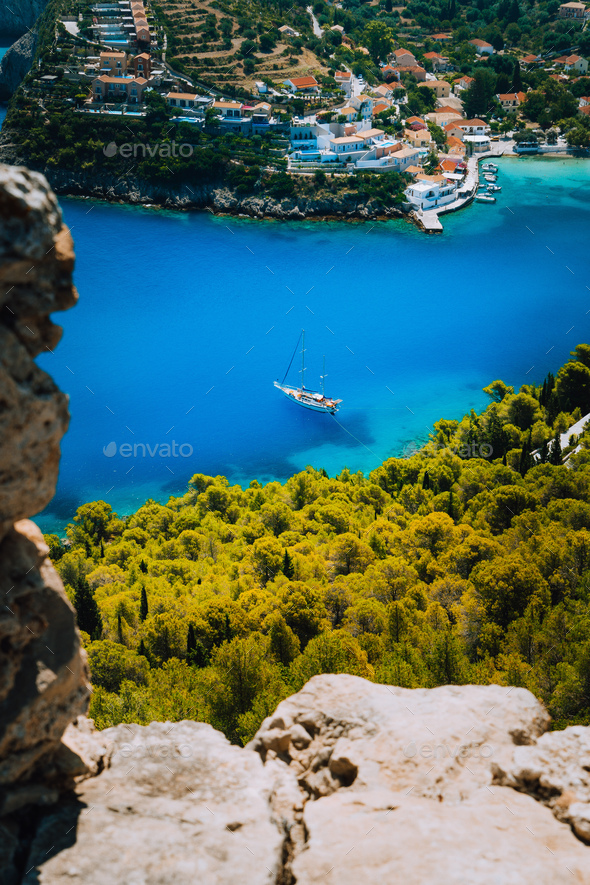 Epic view to blue bay of Assos village Kefalonia from Fortress above. White yacht at anchor in calm - Stock Photo - Images