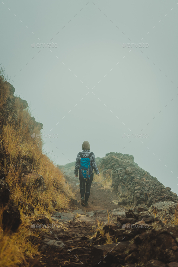 Woman hiker on the cobbled misty path on the mountain crest on Santo Antao island, Cape Verde - Stock Photo - Images