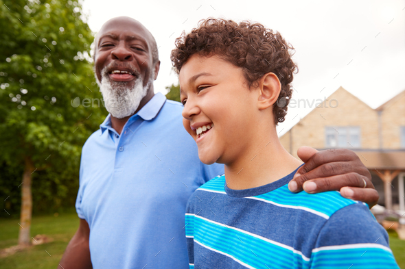 Grandfather With Grandson Walking In Garden At Home - Stock Photo - Images