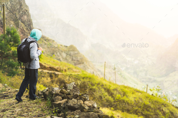 Traveler with backpack staying on the edge of path leading through rural landscape with mountains - Stock Photo - Images