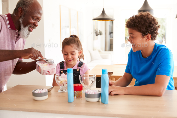 Grandfather Serving Ice Cream To Grandchildren In Kitchen - Stock Photo - Images