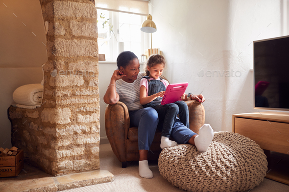 Grandmother Sitting In Chair With Granddaughter Watching Movie On Digital Tablet Together - Stock Photo - Images