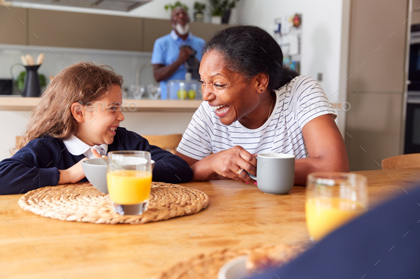 Grandparents Sitting In Kitchen With Grandchildren Eating Breakfast Before Going To School - Stock Photo - Images