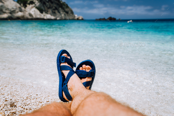 Young male crossed feets in blue flip-flop sandal sunbathing on sea beach - Stock Photo - Images