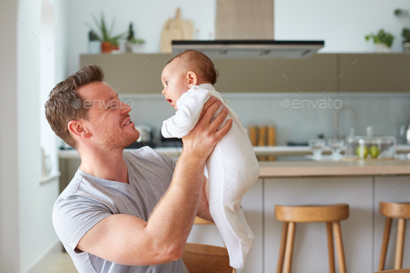 Loving Father Holding 3 Month Old Baby Daughter In Kitchen At Home - Stock Photo - Images