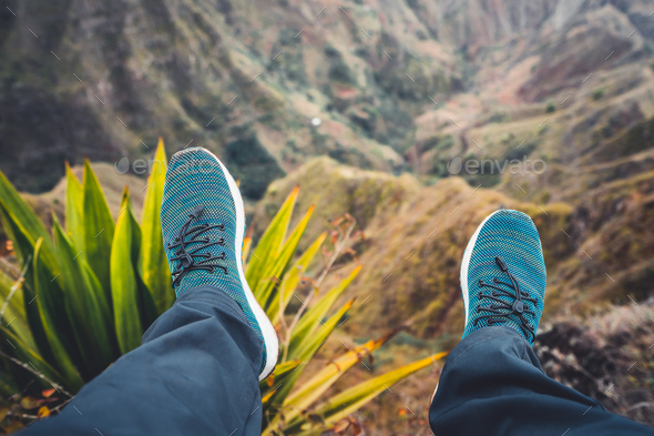 Feet of traveler streching down his legs over breathtaking mountain landscape with mountain peaks - Stock Photo - Images