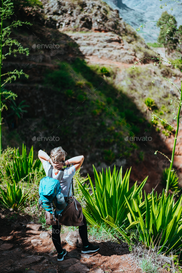 Woman with camera and backpack in front of the arid fins of rocks on Santo Antao island, Cabo Verde - Stock Photo - Images