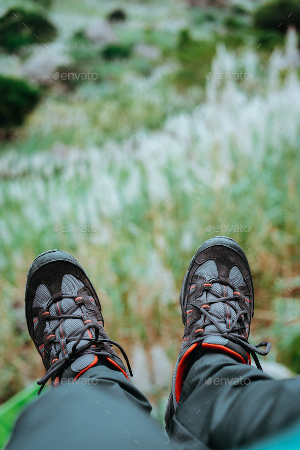 Hanging feet with trekking footwear over hill with sugarcane plants. Santo Antao Island, Cape Verde - Stock Photo - Images