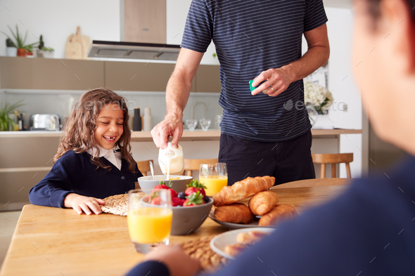 Father In Kitchen Helping Children With Breakfast Before Going To School - Stock Photo - Images