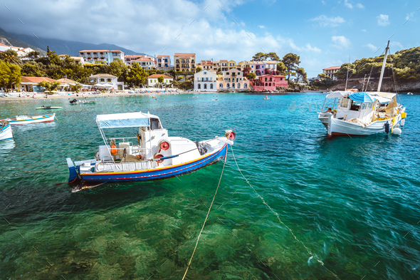 Assos village on Kefalonia island, Greece. White blue local boats at anchor in the emerald rippled - Stock Photo - Images