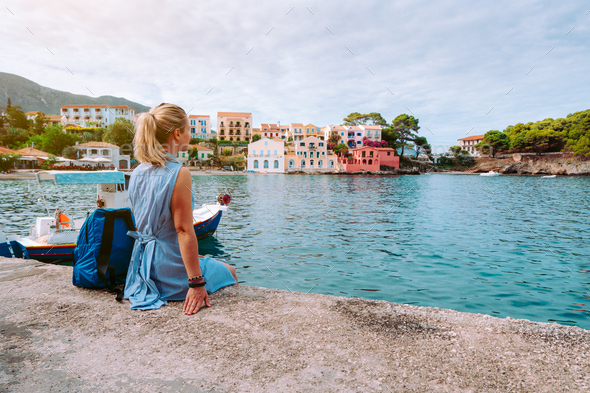 Woman in blue dress sitting on the pier and looking to the picturesque bay. Assos village with - Stock Photo - Images