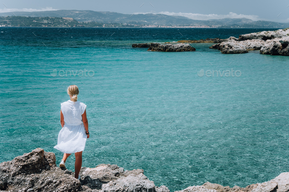 Jung adult women in white dress on summer vacation in front of sea coast landscape of small beach - Stock Photo - Images