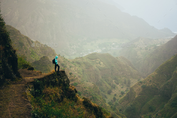 Hiker with backpack on the mountain top. Rocky terrain of a incredible panorama view of high - Stock Photo - Images