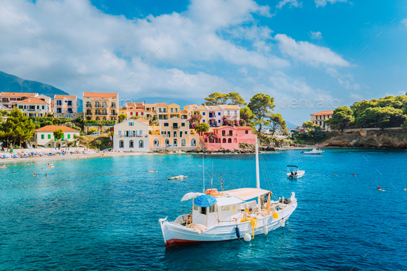 View of beautiful bay of Assos village with fishing boat at anchor in front and clouds in background - Stock Photo - Images