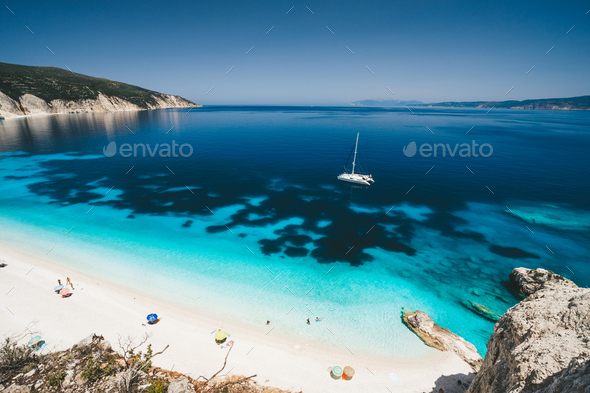 Beach leisure activity. Fteri bay, Kefalonia, Greece. White catamaran yacht in clear blue sea water - Stock Photo - Images