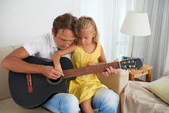 Father and daughter playing guitar - Stock Photo - Images