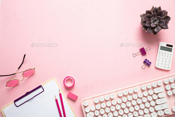 Computer keyboard and succulent plant against pink background - Stock Photo - Images