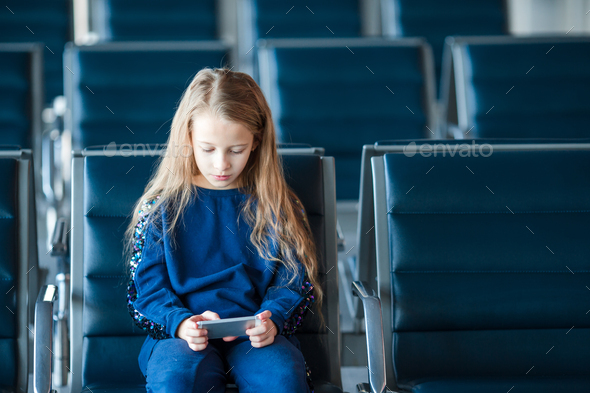 Little adorable girl in airport waiting for boarding playing with laptop - Stock Photo - Images