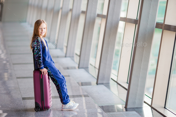 Adorable little girl in airport near big window - Stock Photo - Images