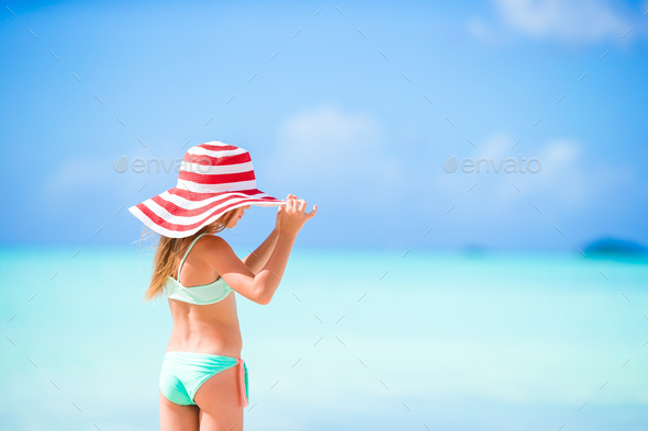 Adorable little girl in big red hat on the beach - Stock Photo - Images