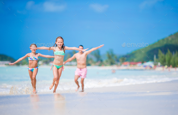 Father and little kids enjoying beach summer tropical vacation. Family playing on the beach - Stock Photo - Images