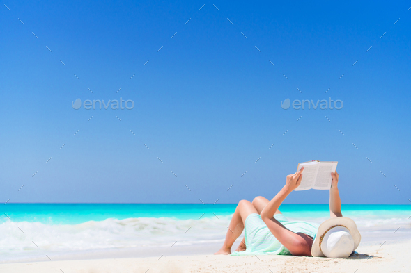 Young woman reading book during tropical white beach - Stock Photo - Images