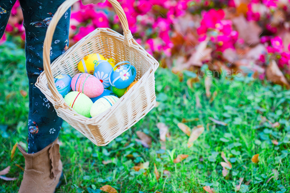 Closeup basket full of colorful Easter eggs in kids hands - Stock Photo - Images