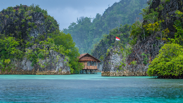 Bamboo Hut between some Rocks under Rain in Bay with Indonesian Flag, Pianemo Islands, Raja Ampat - Stock Photo - Images