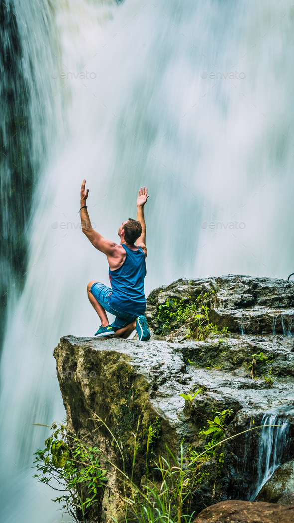 Man sitting in Front of Tegenungan Waterfall near Ubud raising hands and rhapsodize it, Bali - Stock Photo - Images