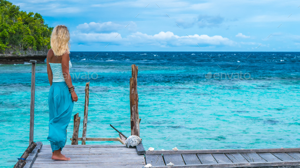 Blond Girl Staying on Wooden Pier of an Homestay looking into blue ocean, Gam Island, West Papuan - Stock Photo - Images