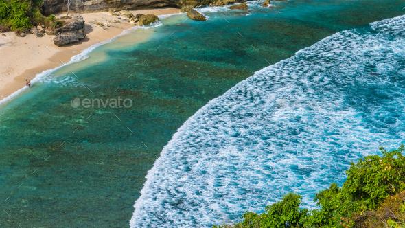 Couple on beautiful Atuh Beach with White Long Waves, Nusa Penida, Bali, Indonesia - Stock Photo - Images