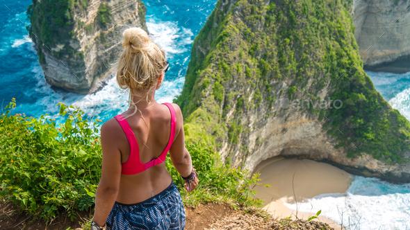 Girl on Cliff at Manta Bay or Kelingking Beach, Nusa Penida Island, Bali, Indonesia - Stock Photo - Images