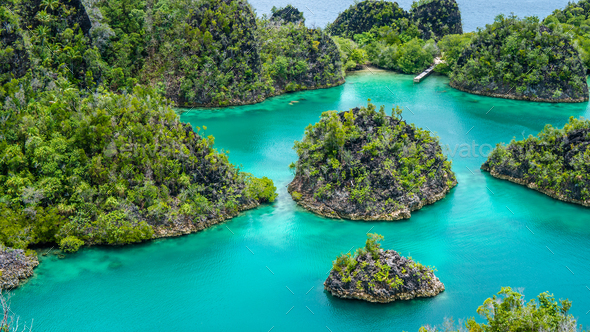 Group of Painemo Island surrounded by Blue Lagoon, Ocean, Raja Ampat, West Papua, Indonesia - Stock Photo - Images