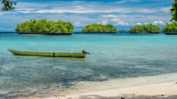Papua Local Boat, Beautiful Blue Lagoone near Kordiris Homestay, Small Green Island in Background - Stock Photo - Images