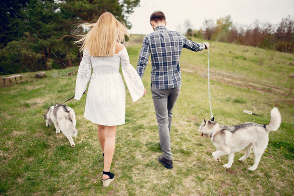 Beautiful couple in a summer forest with a dogs - Stock Photo - Images