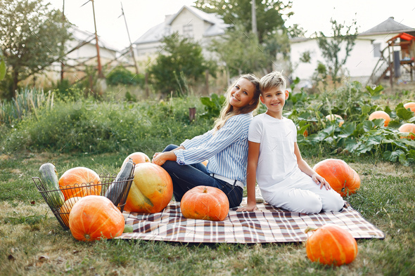 Mother and son sitting on a garden near many pumpkins - Stock Photo - Images